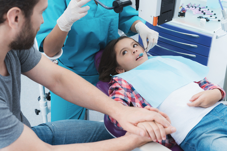 A female dentist is treating a girl. She is sitting on the dental chair. She is afraid and her father holds her hand.