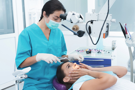 A female dentist is treating a patient. She sits on the dental chair and is afraid.