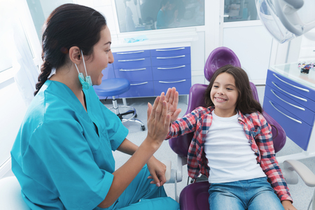 The womans doctor has finished treating the girl. She is happy and gives the doctor high five.
