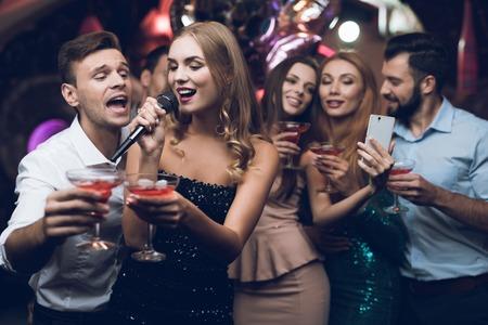Una mujer con un vestido negro canta canciones con sus amigos en un club de karaoke. Sus amigos se autofotos.