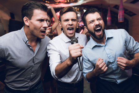 Three men sing at a karaoke club. Young people have fun in a nightclub. They are very cheerful and they smile. Stock Photo