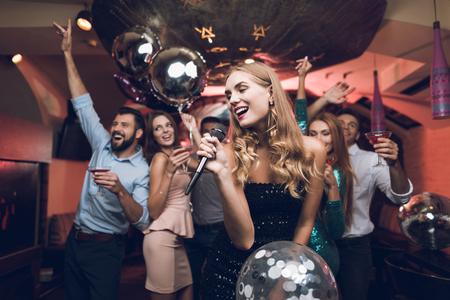 Jonge mensen vermaken zich in een nachtclub en zingen in karaoke. Op de voorgrond staat een vrouw in een zwarte jurk. Stockfoto
