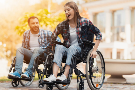 A man and a woman on wheelchairs ride around the park. They arranged a race in wheelchairs.