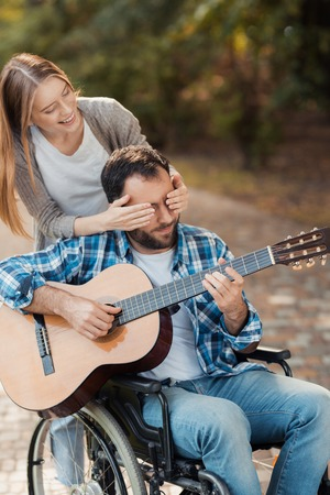A man on a wheelchair playing guitar in the park. A woman came to him from behind and closed her eyes with her hands.