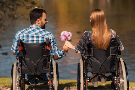 A couple of invalids on wheelchairs met in the park. A man and a woman are holding a bouquet of flowers.