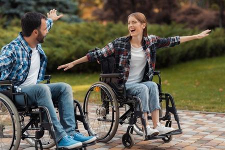 Un homme et une femme en fauteuil roulant se promènent dans le parc. Ils ont mis leurs mains de côté et se sont moqués. Banque d'images