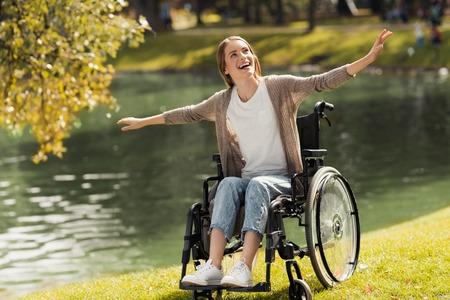 湖の岸辺に車椅子の女性が座っています。彼女は彼女の腕を広げるし、笑った。 写真素材