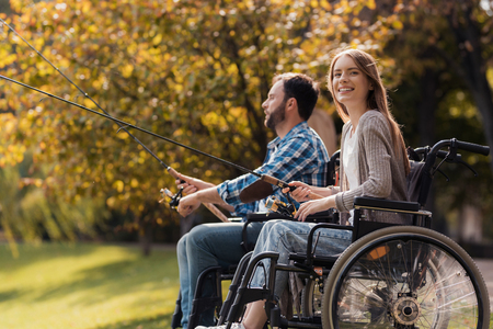 A woman and a man in wheelchairs are sitting on the lake shore. They have spinners in their hands and they are fishing.