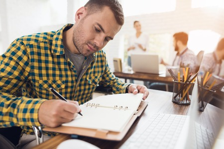 A man in a wheelchair writes with a pen in a notebook. He is working in a bright office.