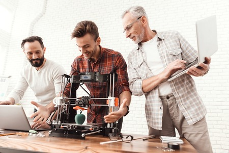 Two men set up a 3d printer, an elderly man holds a laptop in his hands and watches the process. Foto de archivo