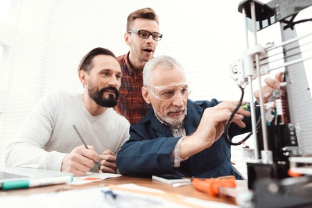 Three engineers print the details on the 3d printer. An elderly man controls the process. Two others follow the process.