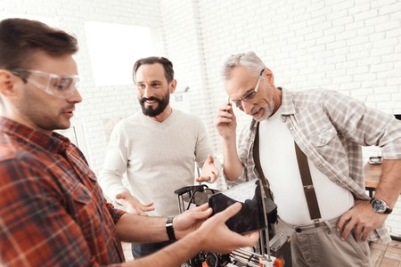 Three men set up a self-made 3d printer to print the form. They are checking the 3d model of the tablet. Stock Photo