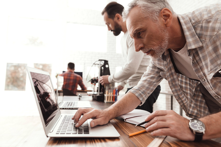 Three men set up a self-made 3d printer to print the form. They check the scribes of the 3d printer on the laptop. Stock Photo