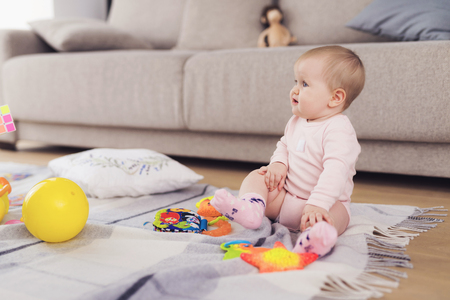 A small beautiful baby sits on the floor and plays with bright, flowery toys. Banque d'images - 90223817