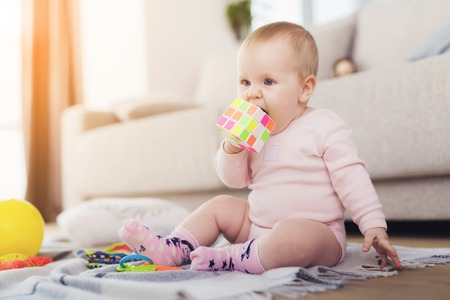 A small beautiful baby sits on the floor and plays with bright, flowery toys. Banque d'images - 90223343
