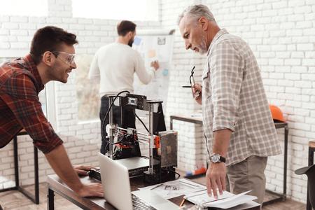3 人の男性は、フォームを印刷する自作の 3 d プリンターを設定します。彼らはノート パソコンで 3 d モデルを確認します。
