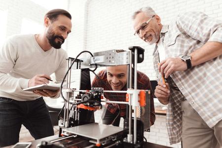 3 人の男性は、フォームを印刷する自作の 3 d プリンターを設定します。彼らは最初の時間のためのデバイスを起動する準備をしています。