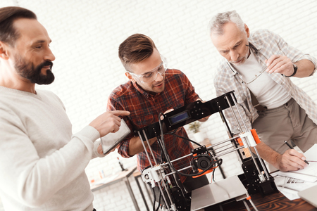 3 人の男性は、フォームを印刷する自作の 3 d プリンターを設定します。彼らは起動し、印刷するためのプリンターを準備します。