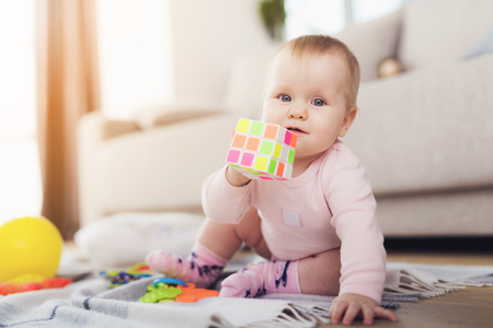 A small beautiful baby sits on the floor and plays with bright, flowery toys. Stock Photo