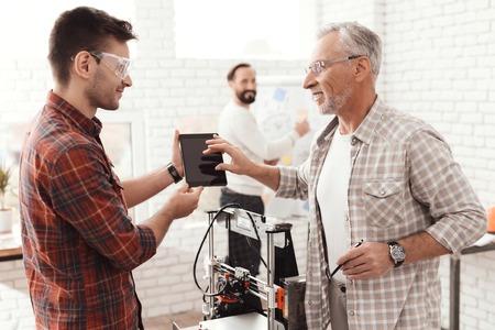3 人の男性は、フォームを印刷する自作の 3 d プリンターを設定します。タブレットの 3 d モデルをチェックしています。