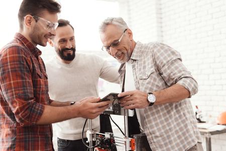 세 사람이 양식을 인쇄하기 위해 자체 제작 된 3D 프린터를 설치했습니다. 그들은 태블릿의 3D 모델을 검사하고 있습니다.