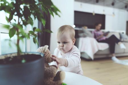赤ちゃんが出席しました。女性が電話で話しているが、彼女の子供は床にクロール、再生されます。 写真素材 - 90223689