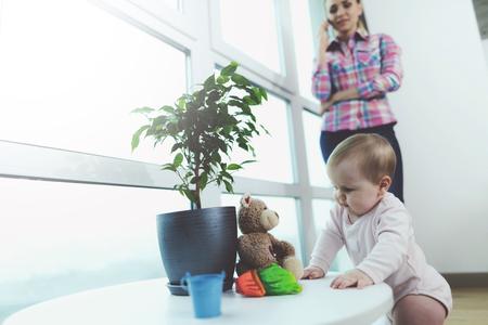赤ちゃんが出席しました。女性が電話で話しているが、彼女の子供は床にクロール、再生されます。