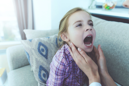 The little girl fell ill. A doctor came to her and examined her throat. Reklamní fotografie