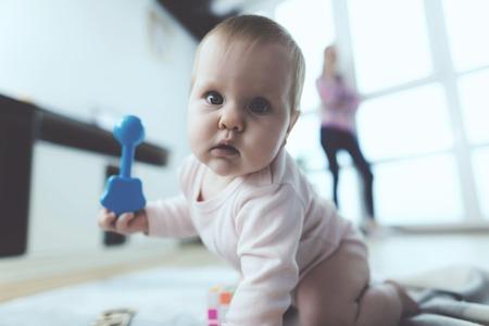 赤ちゃんが出席しました。女性が電話で話しているが、彼女の子供は床にクロール、再生されます。 写真素材 - 90223723