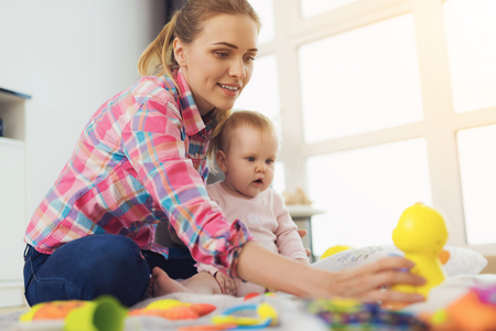 A woman in a pink shirt sits on the floor in living room and plays with her little child. Child really likes to play.