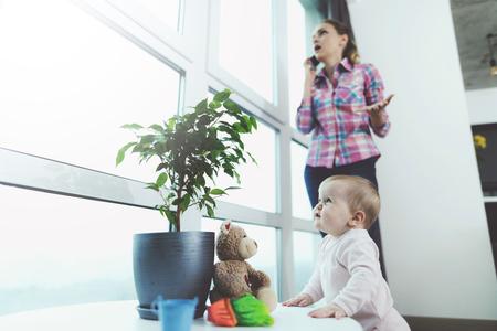赤ちゃんが出席しました。女性が電話で話しているが、彼女の子供は床にクロール、再生されます。 写真素材 - 90226704