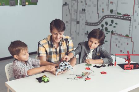 若い男は、二人の少年ロボットをアセンブルする方法を示しています。彼らは観察し、関心を持つヘルプ