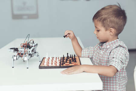 A little boy is playing chess with a gray robot. Robot plays for whites