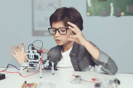 A small nerd in glasses is holding a robot. He enthusiastically looks at his creation