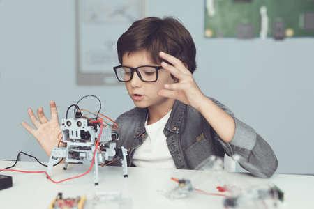 Een kleine nerd in een bril houdt een robot vast. Hij kijkt enthousiast naar zijn creatie