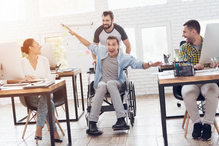A colleague rolls a person in a wheelchair around the office. They have fun and laugh. Banco de Imagens