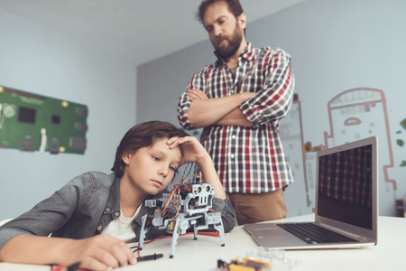 The boy hurt the robot. A man severely chastises the boy, explaining to him his mistakes