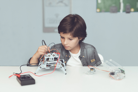 The boy creates a robot. He measures his data with a multimeter. The boy observes the measurements