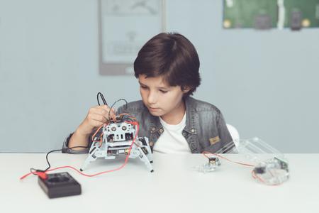 El chico crea un robot. Él mide sus datos con un multímetro. El chico observa las medidas