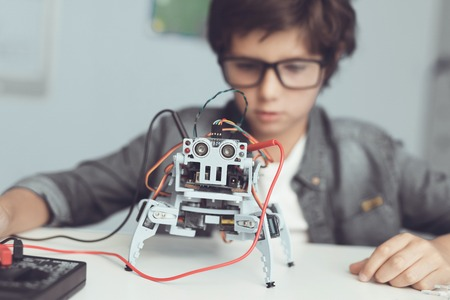 A small nerd in glasses is holding a robot. He looks carefully at his creation Banque d'images