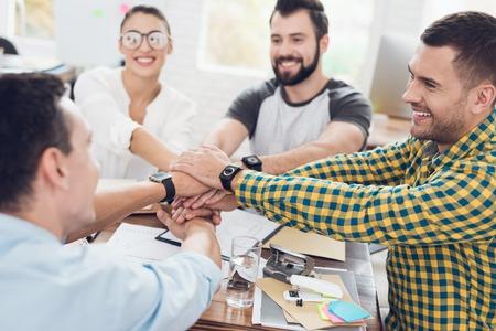 Een groep jongeren die iets op kantoor bespreken. Ze laten een teamwork zien.