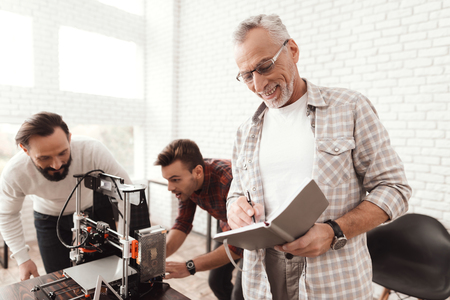 Three men set up a self-made 3d printer to print the workpiece. An elderly man with a notebook watching his colleagues.