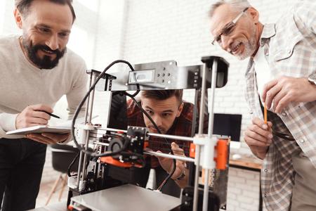 3人の男性が自作の3Dプリンターを設置してフォームを印刷しました。彼らは初めてデバイスを起動する準備をしています。