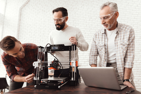 Three men set up a self-made 3d printer to print the workpiece. An elderly man with a laptop is watching his colleagues. Stock Photo