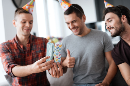 Men in birthday hats are showing to each other presents. Stock Photo