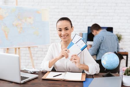 De reisagent bewaart tickets voor het vliegtuig in het reisbureau.