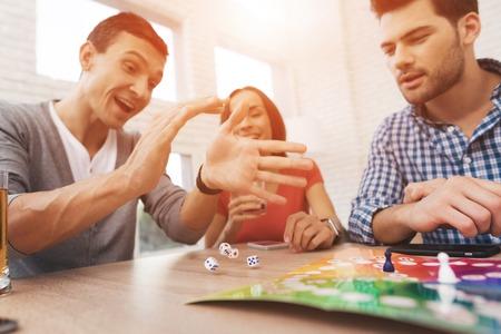 Junge Leute spielen ein Brettspiel mit einem Würfel und Chips Standard-Bild - 90420606