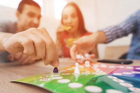 Young people play a board game using a dice and chips. Stock Photo