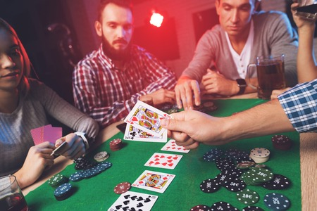 Young people play poker at the table. Reklamní fotografie