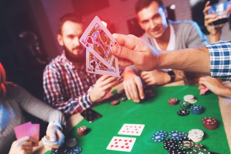Young people play poker at the table. Archivio Fotografico